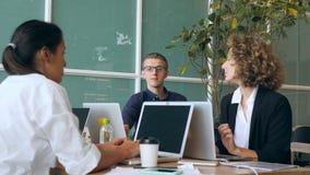 Jeune programmeur Geek dans le bureau jouant l'avion de papier tandis que d'autres personnes travaillent 4K banque de vidéos