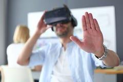 Jeune programmeur masculin de logiciel examinant un nouvel APP avec des verres de la réalité virtuelle 3d dans le bureau Photo libre de droits