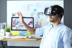 Jeune programmeur masculin de logiciel examinant un nouvel APP avec des verres de la réalité virtuelle 3d dans le bureau Photos stock