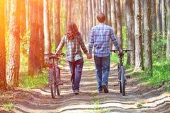 Jeune promenade de couples avec des bicyclettes Image stock