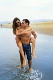 Jeune promenade de couples dans l'océan Photographie stock libre de droits