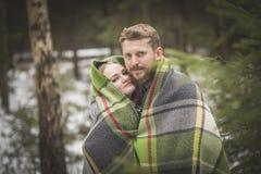 Jeune promenade de forêt d'hiver de couples dans une couverture chaude Photo stock