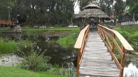 Jeune promenade de sourire de fille sur le pont en bois de vintage au-dessus du courant 4K banque de vidéos