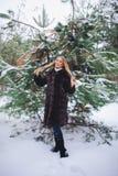 Jeune promenade modèle de fille dans la forêt d'hiver Photo stock