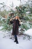 Jeune promenade modèle de fille dans la forêt d'hiver Image stock