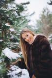 Jeune promenade modèle de fille dans la forêt d'hiver Photo libre de droits