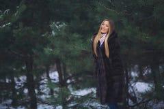 Jeune promenade modèle de fille dans la forêt d'hiver Image libre de droits