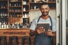 Jeune propriétaire masculin de café regardant le comprimé numérique photographie stock libre de droits