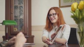 Jeune psychologue féminin roux attirant en verres consultant son patient, montrant l'information sur le comprimé clips vidéos