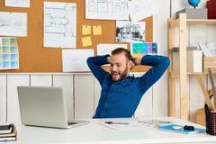 Jeune réjouissance réussie d'homme d'affaires, séance sur le lieu de travail avec l'ordinateur portable Fond de bureau Image libre de droits