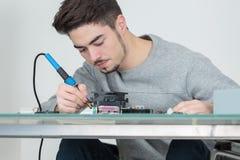 Jeune réparateur beau d'ordinateur concentré sur le travail Photographie stock