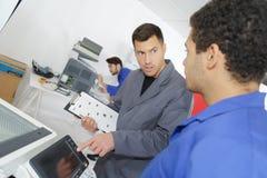 Jeune réparateur de photocopieur avec l'instructeur expérimenté images libres de droits