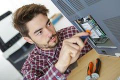 Jeune réparateur travaillant avec le tournevis au centre de service Image stock