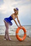 Jeune rétro fille de pin-up avec la coiffure bouclée blonde et beau Image stock