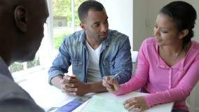 Jeune réunion noire de couples avec le conseiller financier à la maison banque de vidéos