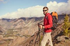Jeune randonneur masculin barbu beau se tenant au bord d'un canyon regardant loin Image stock
