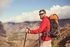 Jeune randonneur masculin barbu beau se tenant au bord d'un canyon regardant loin Photo stock