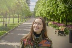 Jeune recherche de rêverie de sourire de femme dans le ciel Photo libre de droits
