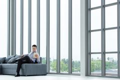 Jeune regard asiatique d'homme d'affaires au comprimé se reposant sur le SMI heureux de sofa photo libre de droits