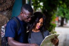 Jeune regard de touristes de couples à la carte image stock