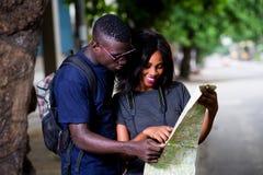 Jeune regard de touristes de couples à la carte photographie stock libre de droits