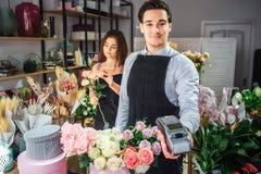 Jeune regard masculin gentil et gai de fleuriste sur le therminal de caméra et d'argent de prise Il se tiennent à la table avec d photo stock