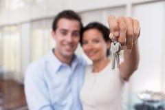 Jeune représentation de sourire heureuse de couples clés de leur nouvelle maison Photos stock