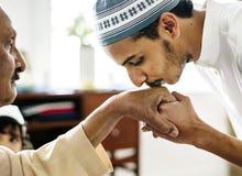 Jeune respect musulman d'apparence d'homme à son père images stock