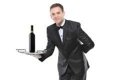 Jeune retenant un plateau avec du vin là-dessus photo libre de droits