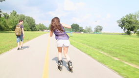 Jeune roller attrayant de femme en parc un beau jour ensoleillé banque de vidéos