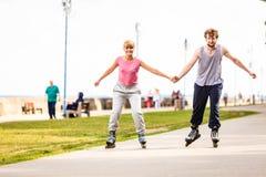 Jeune roller de couples en parc tenant des mains Photos stock