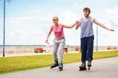 Jeune roller de couples en parc tenant des mains Photographie stock libre de droits