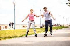 Jeune roller de couples en parc tenant des mains Image libre de droits
