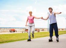 Jeune roller de couples en parc tenant des mains Images libres de droits