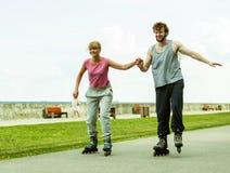Jeune roller de couples en parc tenant des mains Images stock