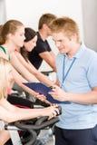 Jeune rotation de gens de gymnastique d'instructeur de forme physique Image libre de droits