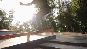 Jeune rouleau dans les glissières noires de vêtements sport par un tuyau dans un skatepark Un jeune athlète exécute un tour sur d clips vidéos