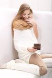Jeune séance blonde aux cheveux longs sur un sofa avec un présent images stock