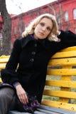 Jeune séance blonde triste sur un banc en stationnement Photo stock