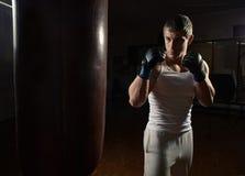 Jeune séance d'entraînement musculaire de boxeur d'homme avec le sac de sable Images stock