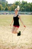 Jeune séance d'entraînement sportive de femme, sautant par-dessus la corde Photo libre de droits