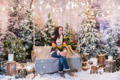 Jeune séance femelle sur un banc ou une oscillation au-dessus des lampes-torches Photographie stock libre de droits