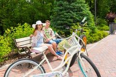 Jeune séance masculine et femelle sur le banc près des vélos Images libres de droits