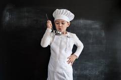 Jeune ` s de garçon tenant le tableau noir proche vérifiant la soupe Jeune garçon de chef Concept de construction créatif pour le image libre de droits
