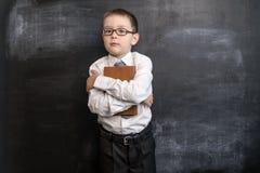 Jeune ` s de garçon tenant un livre près du tableau noir De nouveau au concept d'école Garçon préscolaire futé et intelligent Images stock