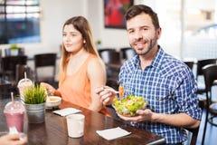 Jeune salade mangeuse d'hommes à un restaurant Photo stock