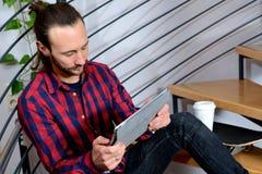 Jeune séance sur les escaliers et la tablette d'utilisation Images stock