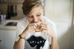 Jeune sandwich mangeur d'hommes caucasien dans la cuisine photos libres de droits