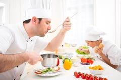 Jeune sauce professionnelle attrayante à échantillon de chef photo stock