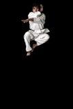 Jeune saut mâle de chasseur de karaté contrasté photographie stock
